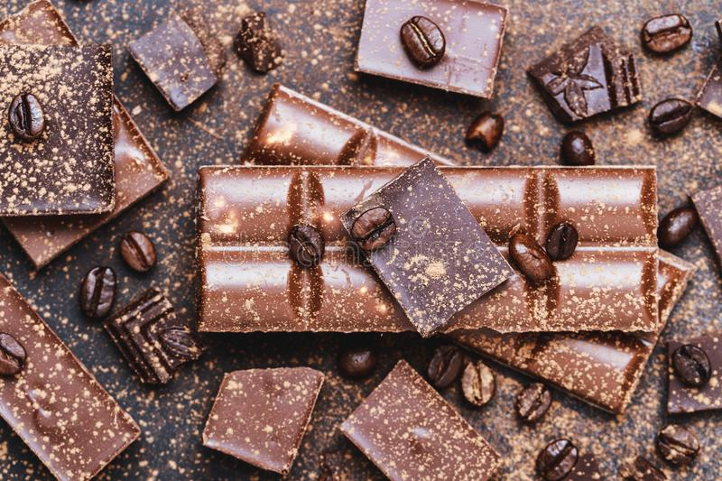 Chocolate bar pieces. Background with chocolate. Sweet food photo concept. The chunks of broken chocolate stock image