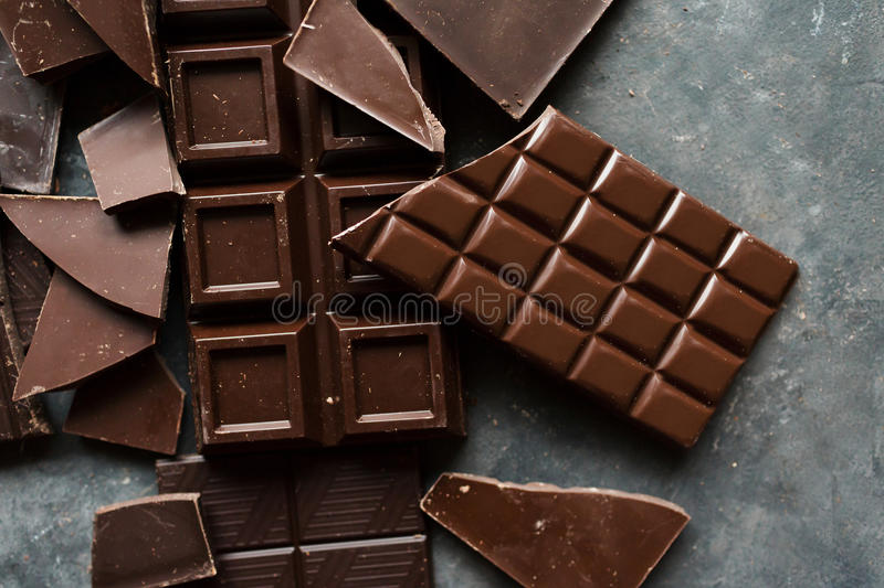 Chocolate bar pieces. A large bar of chocolate on gray abstract background. Slices of chocolate Sweet food photo concept. Copyspace royalty free stock photography