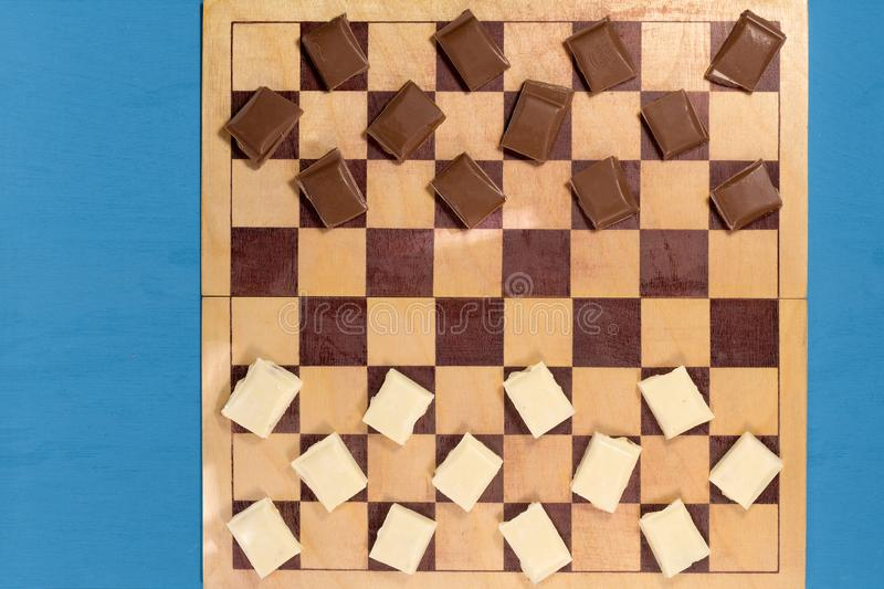 Chocolate bars brown and white on a chessboard. Game, rivalry, competition stock photography