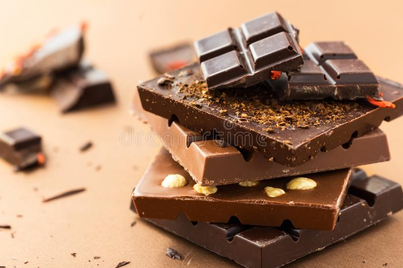 Chocolate bars with nuts, goji berries and coffee beans. Dark and milk chocolate bars on a brown background royalty free stock images