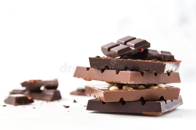 Chocolate bars with nuts, goji berries and coffee beans. Dark and milk chocolate bars on a white background royalty free stock images