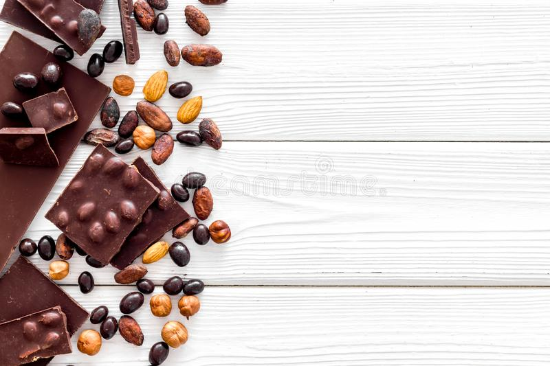 Chocolate bars and nuts on white wooden table background top view mockup royalty free stock images