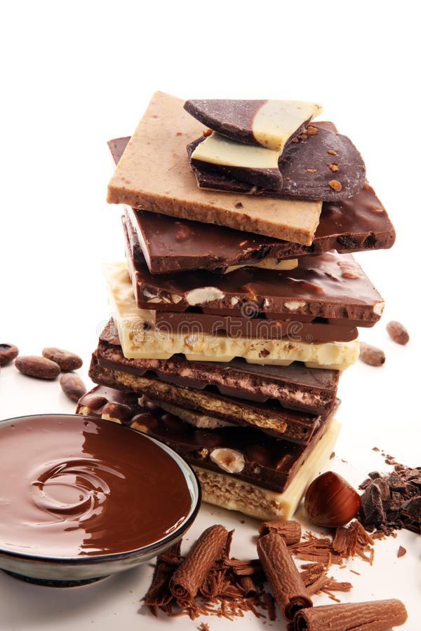Chocolate bars on table with chocolate tower. Chocolate and nuts and choco swirl stock image