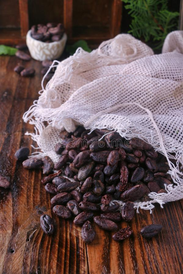 Chocolate beans on wooden table. Raw chocolate beans in sack on wooden table royalty free stock photos