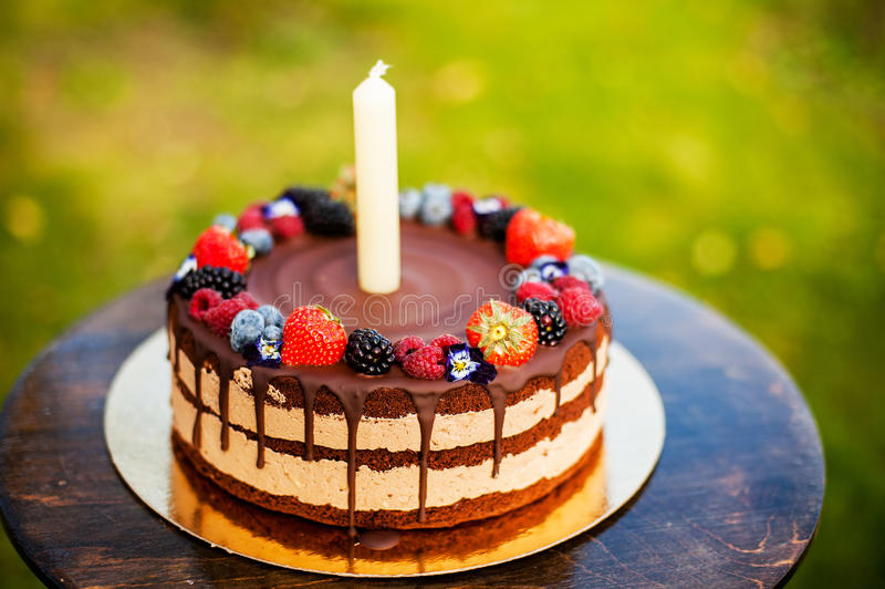 Chocolate and berry cake. Large chocolate and fresh berries birthday cake with a candle royalty free stock photo