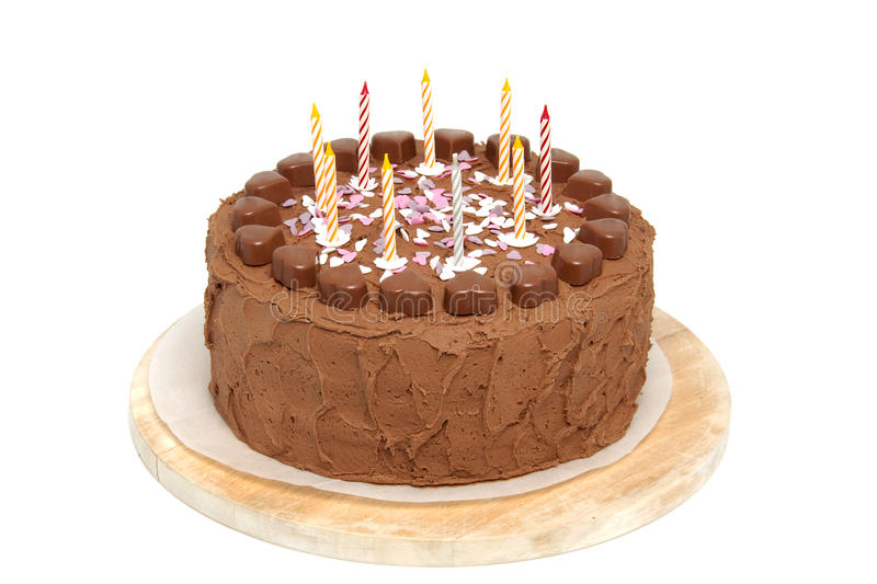 Chocolate birthday cake. With candles on wooden cutting board over white background royalty free stock photo