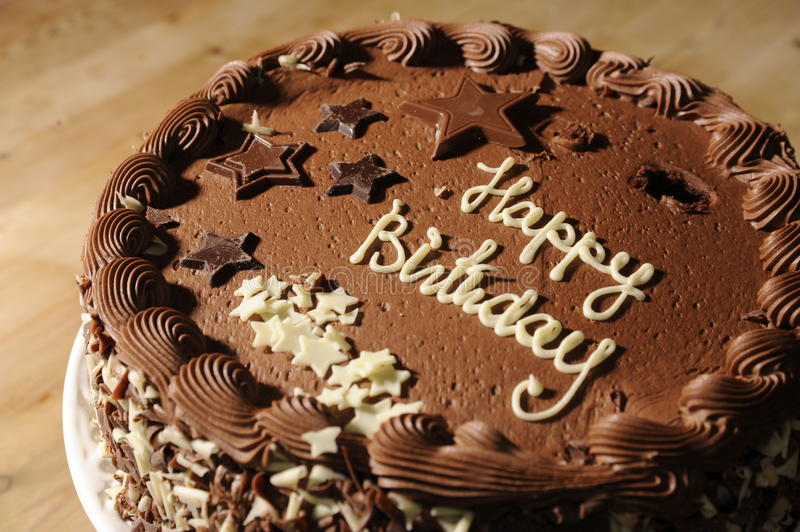 Chocolate Birthday Cake. Delicious fresh Chocolate Birthday Cake on a wooden kitchen table, ready for the party. Shallow depth of field royalty free stock photography
