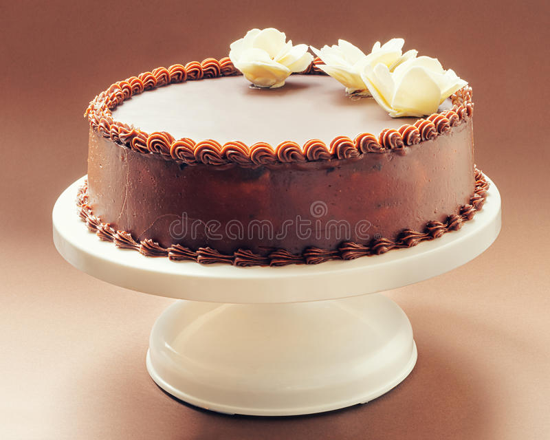 Chocolate Birthday Cake. All chocolate birthday cake, on brown background, decorated with yellow flowers on top royalty free stock photography