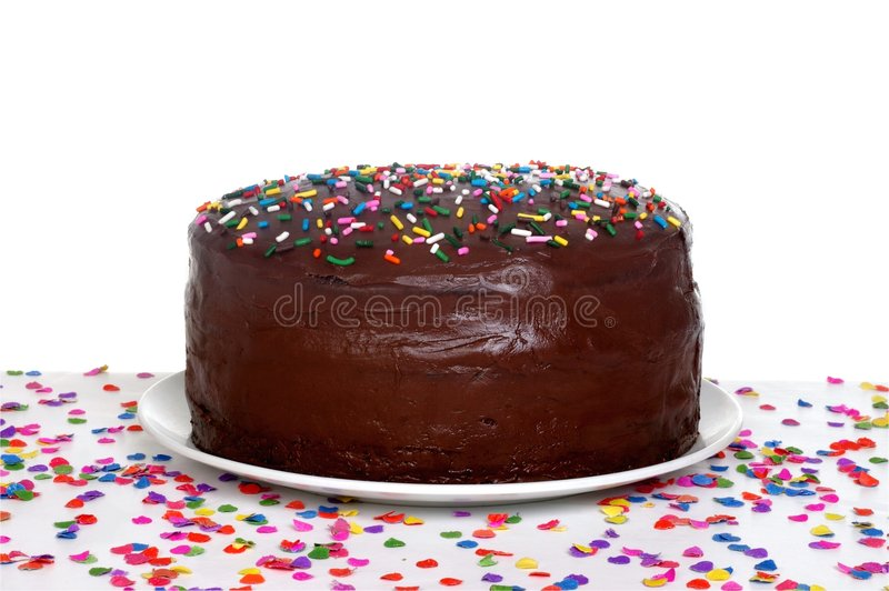 Chocolate Birthday Cake. A chocolate frosted birthday cake topped with colorful sprinkles, sitting on a table full of scattered confetti stock photo