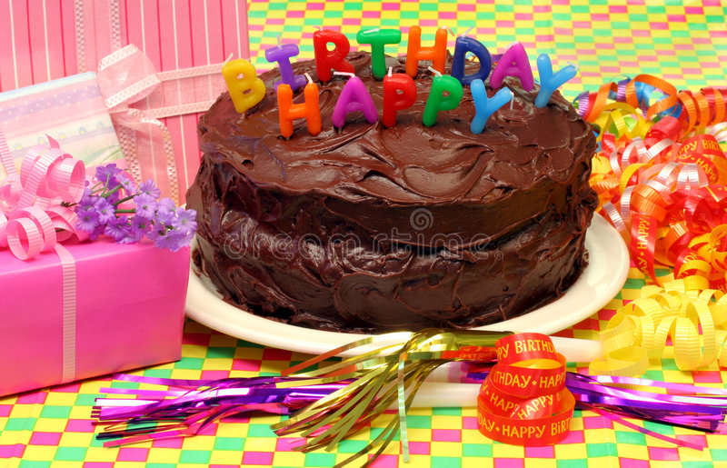 Chocolate Birthday Cake. With Happy Birthday Candles and festive party supplies and gifts all around. Colorful and cheerful royalty free stock image