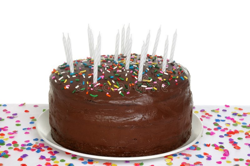 Chocolate Birthday Cake. A chocolate frosted birthday cake with white candles, topped with colorful sprinkles, sitting on a table full of scattered confetti, on stock images
