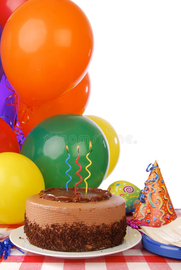 Chocolate birthday cake and balloons stock image