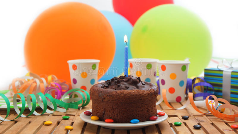 Chocolate birthday cake with a blue candle burning on rustic wooden table with background of colorful balloons, gifts. Plastic cups with candies and white wall royalty free stock photos