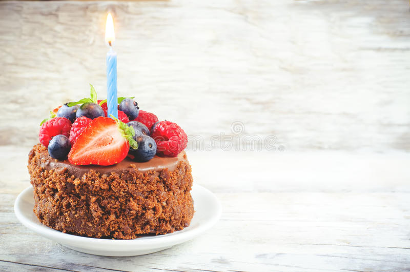 Chocolate birthday cake with candle, raspberries, blueberries an. D strawberries on a white wood background. toning. selective focus on strawberry stock photos