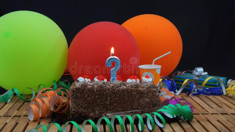 Chocolate birthday cake with candle in the shape of a question mark on rustic wooden table with background of colorful balloons. Gifts, plastic cups and stock image