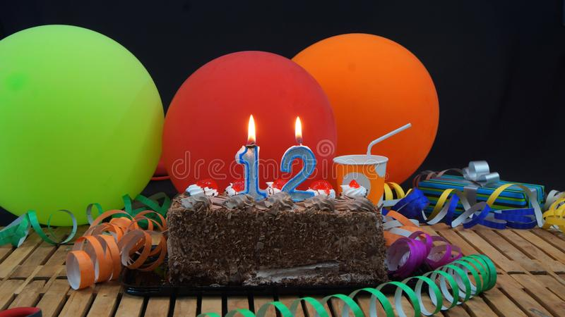 Chocolate birthday 12 cake with candles burning on rustic wooden table with background of colorful balloons. Gifts, plastic cups and streamers with black royalty free stock photos