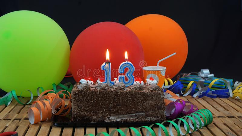 Chocolate birthday 13 cake with candles burning on rustic wooden table with background of colorful balloons stock photos