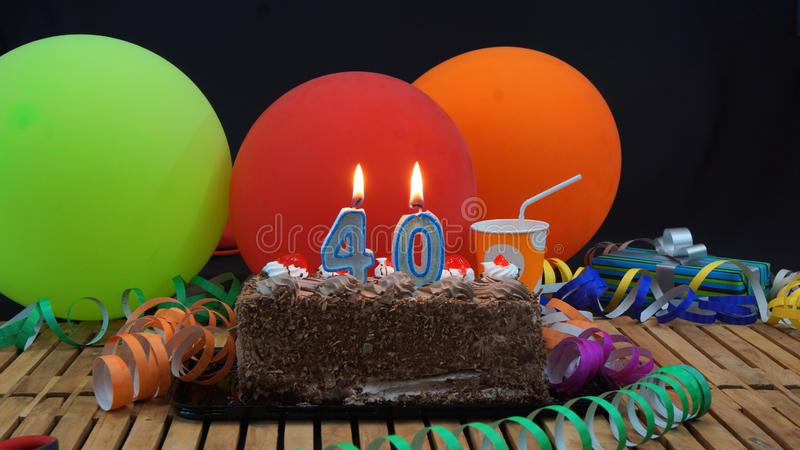 Chocolate birthday 40 cake with candles burning on rustic wooden table with background of colorful balloons stock photos