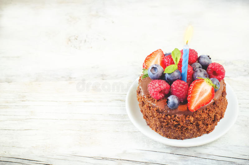 Chocolate birthday cake with candles, raspberries, blueberries a. Chocolate birthday cake with candle, raspberries, blueberries and strawberries on a white wood royalty free stock photo