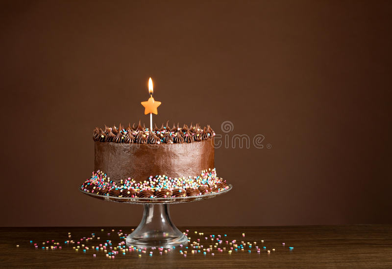 Chocolate Birthday Cake. With colorful sprinkles and candles over a brown background stock image