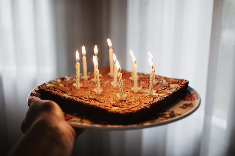 Chocolate birthday cake with eleven candles burning stock images
