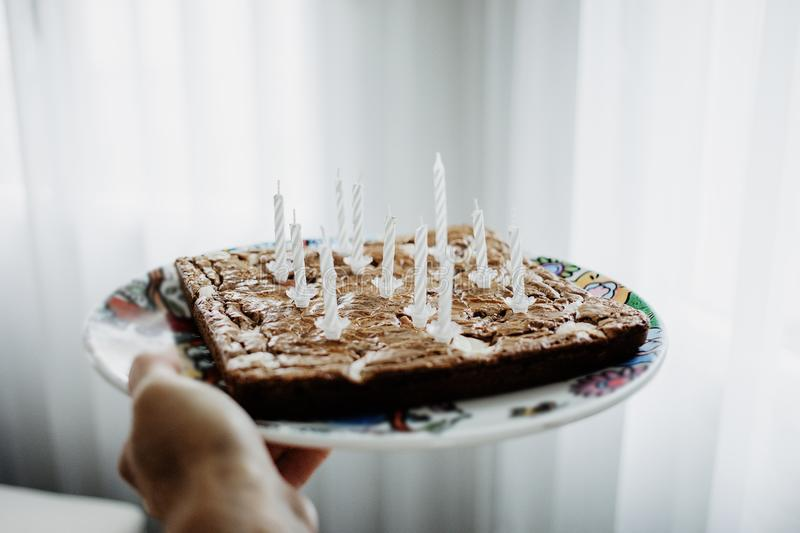 Chocolate birthday cake with eleven white candles. royalty free stock photos