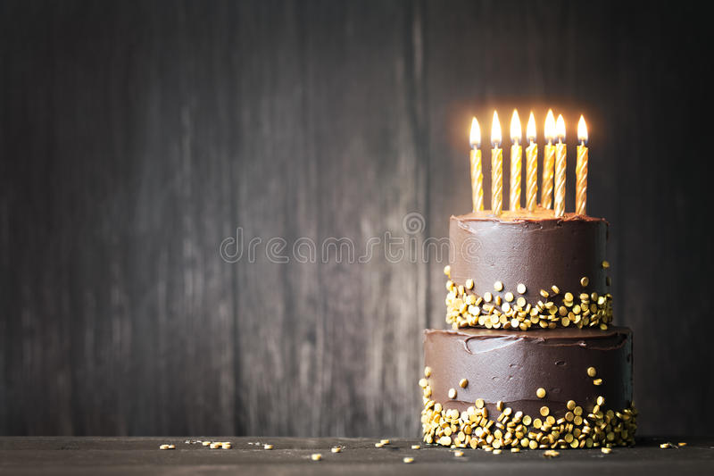 Chocolate birthday cake. With gold candles stock photos