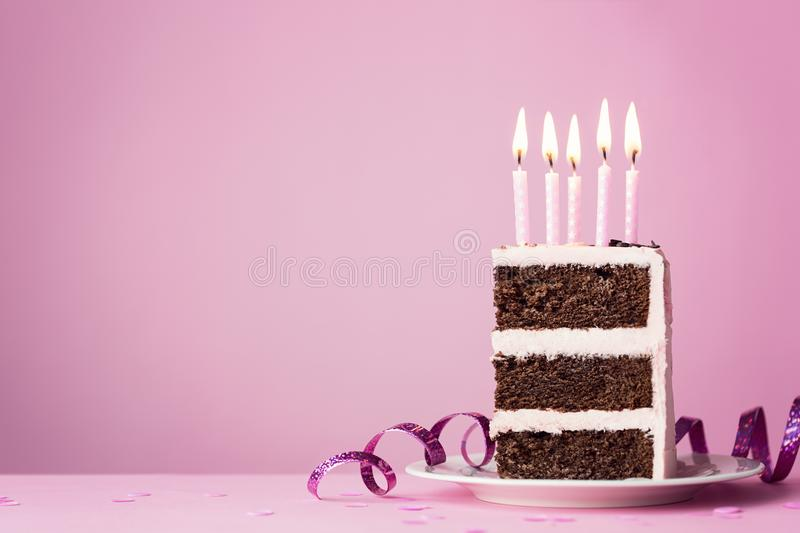Chocolate birthday cake with pink candles. Chocolate birthday cake with pink frosting and candles royalty free stock photos