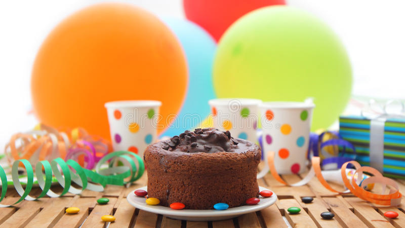 Chocolate birthday cake on rustic wooden table with background of colorful balloons, gifts, plastic cups with candies royalty free stock photography