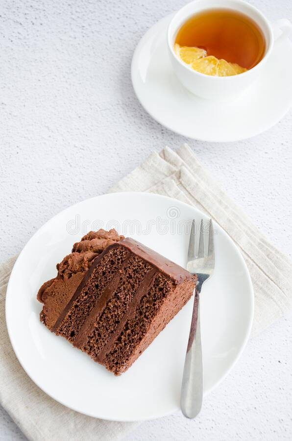 Chocolate Birthday cake. A slice of delicious chocolate cake on a light background. Piece of Cake on a white Plate. Sweet food. Sweet dessert. Vertical stock image