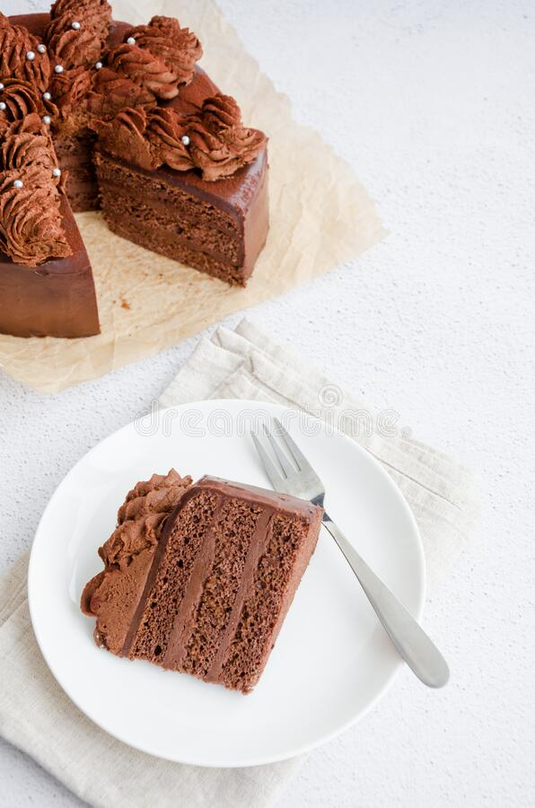 Chocolate Birthday cake. A slice of delicious chocolate cake on a light background. Piece of Cake on a white Plate. Sweet food. Sweet dessert. Vertical royalty free stock images