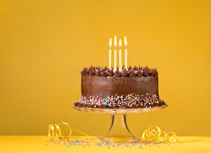 Chocolate Birthday Cake on Yellow. Chocolate birthday cake with colorful sprinkles and candles over yellow background stock photography