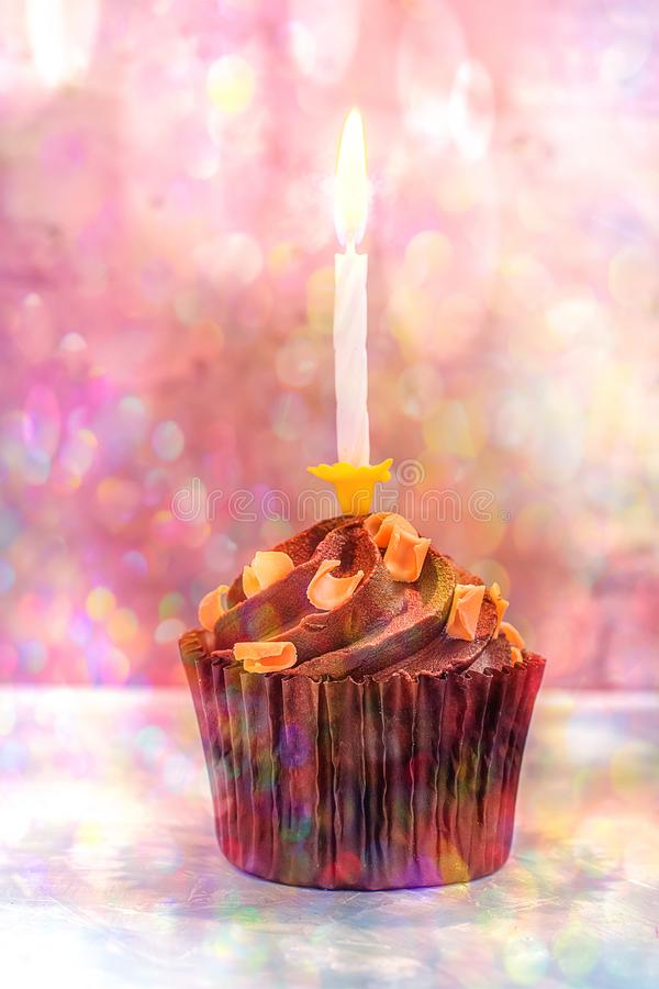 Chocolate Birthday Cupcake with Buttercream Caramel Swirl Sprinkles. Single Lit Burning Candle. Colorful Confetti Lights Flare stock image