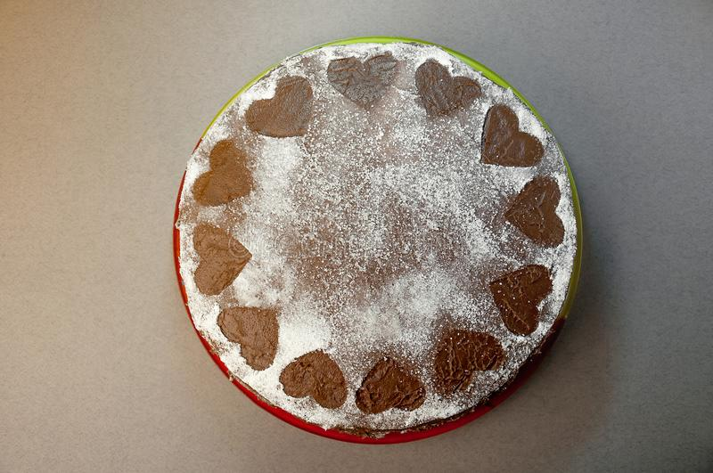 Chocolate Biscuit Cake with Cocoa Cream with Small Hearts from Powdered Sugar. Dessert. Valentine`s Day Concept. Flat Lay Top Vie stock photo