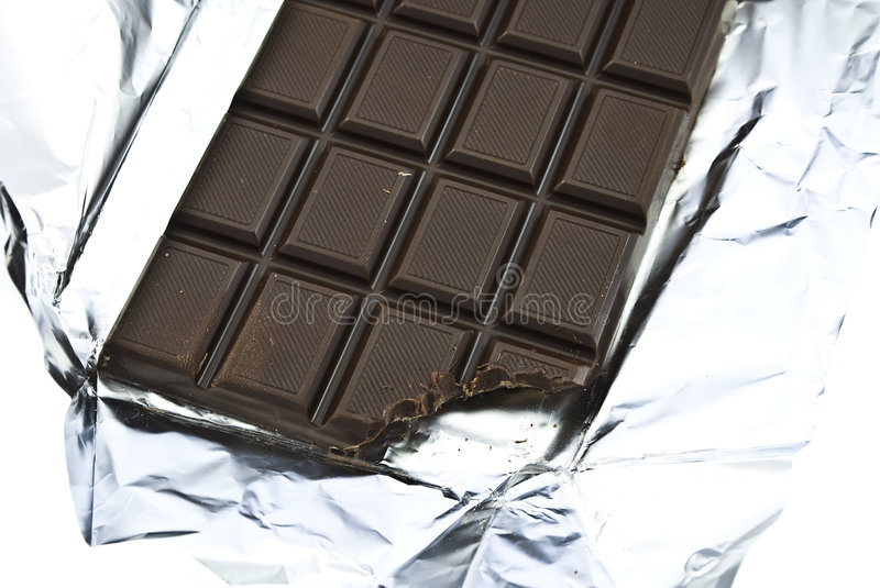 Chocolate bite on a foil royalty free stock images