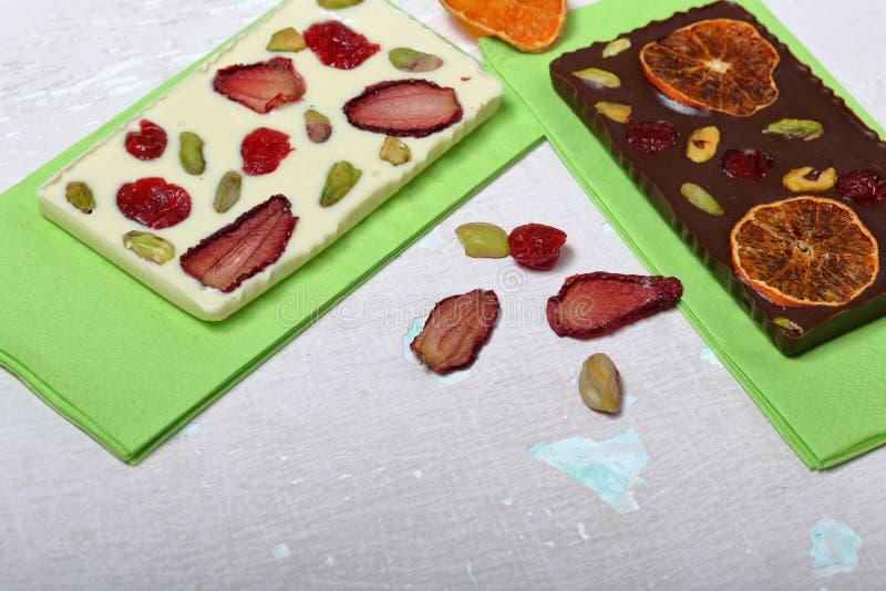 Chocolate branco e preto caseiro Decorado com fatias de laranja, de morangos, de cerejas e de pistaches secados foto de stock royalty free