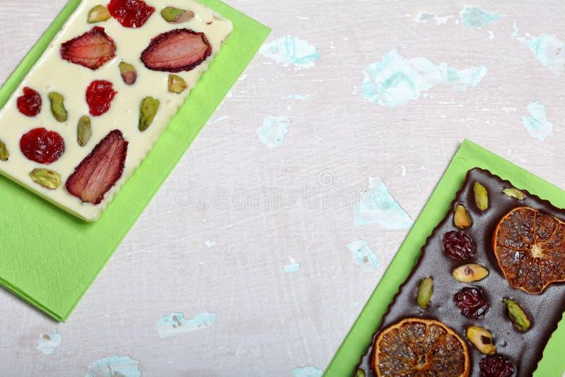 Chocolate branco e preto caseiro Decorado com fatias de laranja, de morangos, de cerejas e de pistaches secados foto de stock