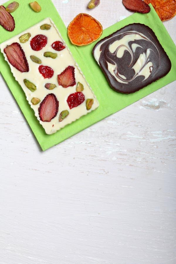 Chocolate branco e preto caseiro Decorado com fatias de laranja, de morangos, de cerejas e de pistaches secados fotos de stock