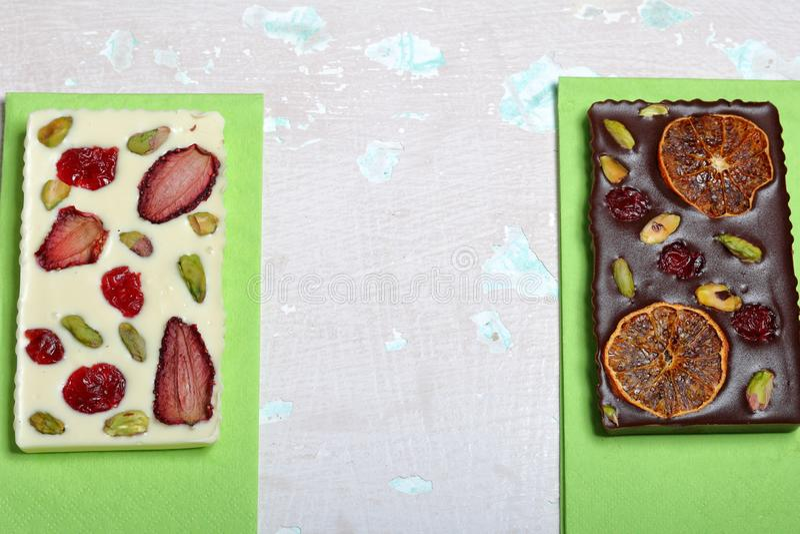 Chocolate branco e preto caseiro Decorado com fatias de laranja, de morangos, de cerejas e de pistaches secados fotografia de stock
