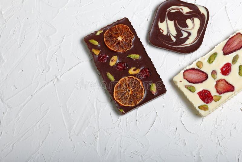 Chocolate branco e preto caseiro Decorado com fatias de laranja, de morangos, de cerejas e de pistaches secados fotografia de stock royalty free