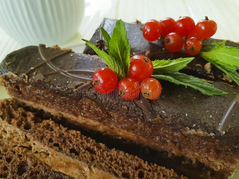 Chocolate brown cake, red currant, mint tasty lunch cutting baked dish seasoning pastry plate white wooden. Chocolate cake brown red currant mint plate on white stock images