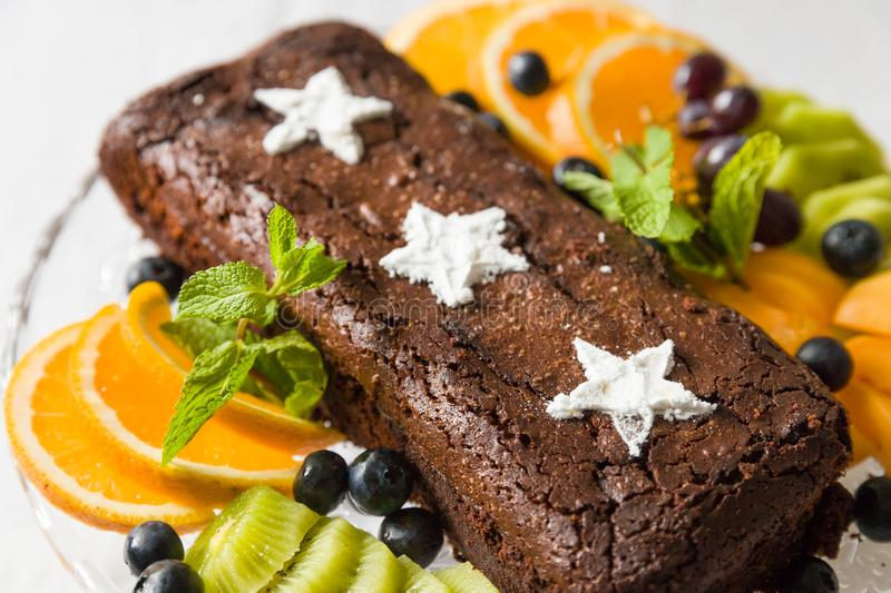 Chocolate brownie cake with fresh blueberry, white sugar stars and oranges. Homemade chocolate cake served with fruit stock image