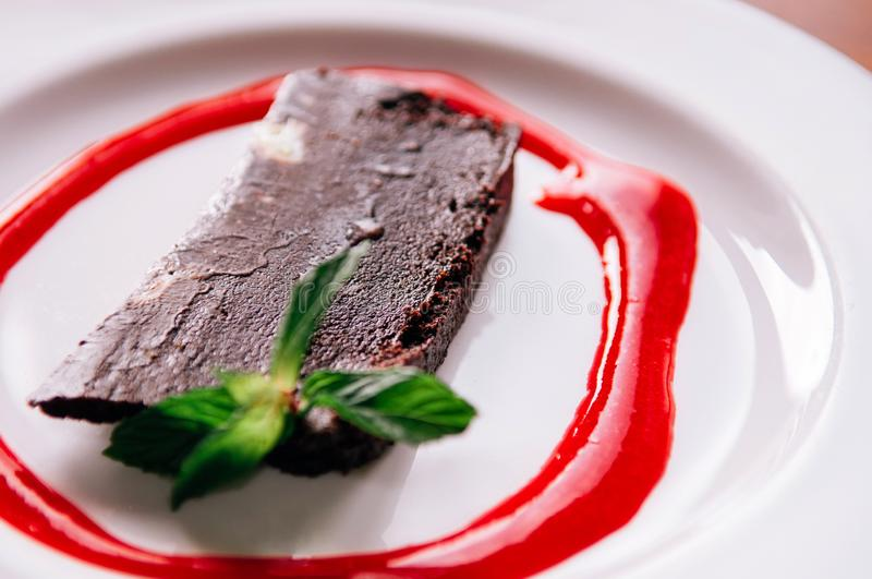 Chocolate Brownie fudge cake with red raspberries sauce and mint leaves stock photos
