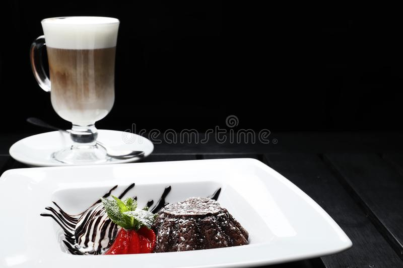 Chocolate brownie with ice cream on a black wooden background royalty free stock photography