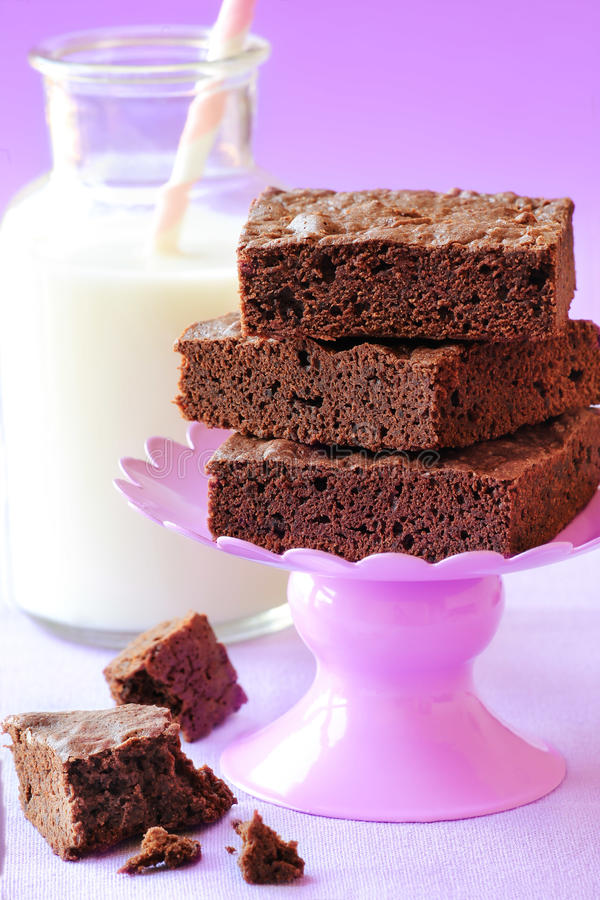 Chocolate brownies. Delicious homemade double chocolate brownies on purple stand with milk at the background stock image