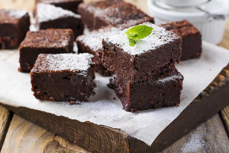 Chocolate brownies with powdered sugar and cherries on a dark wooden background. royalty free stock photography