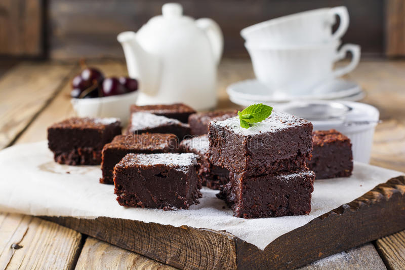 Chocolate brownies with powdered sugar and cherries on a dark wooden background. stock photography