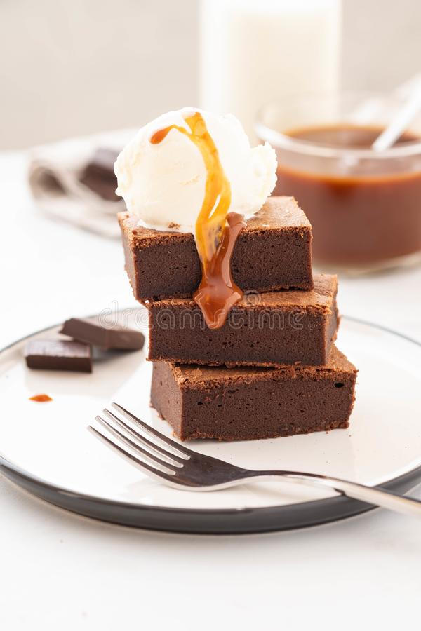 Chocolate brownies with salted caramel, vanilla ice cream. Copy space. stock photos