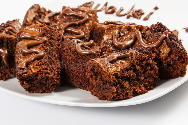 Chocolate brownies on white plate stock images