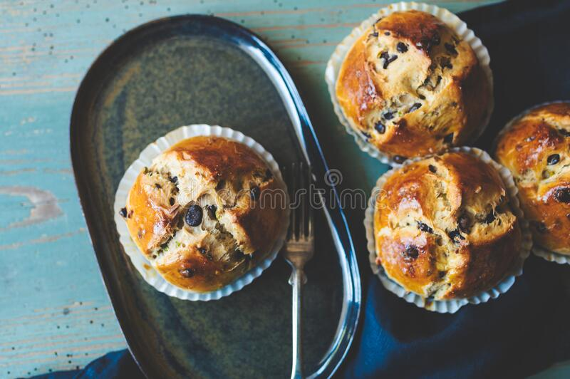 Chocolate buns in muffin tray. Four chocolate buns in white muffin tray, a plate on a dark blue napkin, an old blue wooden board as a background stock images